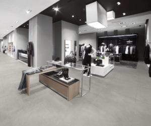 clothing store with grey commercial tile flooring, grey walls and bright lighting on the ceiling.