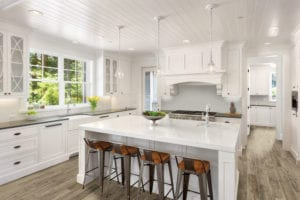 Kitchen tiles being used on the floor and backsplash in a white kitchen with an island and bright lights